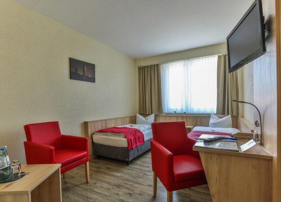 Rügenhotel Zweibettzimmer Landseite Betten Sessel Fernseher